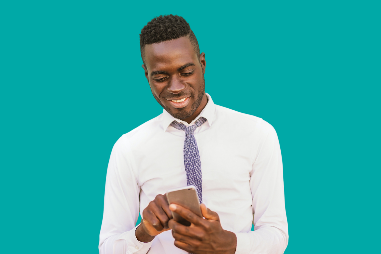 African American Man in white shirt looking down at mobile phone